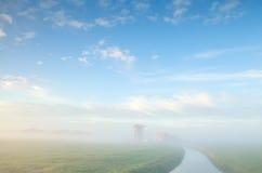 Nebelhafter Morgen auf niederländischem Ackerland mit Windmühle Lizenzfreies Stockfoto