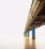 Nebelhafter Morgen des Herbstes auf hölzernem Pier über Meer Krise, dunkle Atmosphäre Lizenzfreies Stockfoto