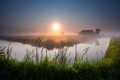 Nebelhafter Sonnenaufgang über Fluss im Ackerland Stockfotos