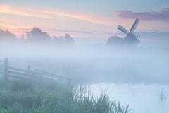 Nebelhafter Sonnenaufgang über niederländischer Windmühle auf Ackerland Lizenzfreies Stockfoto