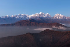 Nebelhafter Sonnenaufgang über schneebedeckter Gebirgslandschaft mit Stockfoto
