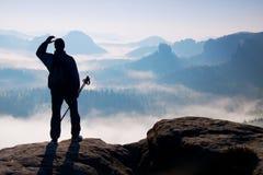 Nebelhafter Tag in den felsigen Bergen Schattenbild des Touristen mit Pfosten in der Hand Wandererstand auf felsigem Standpunkt ü Stockfotografie