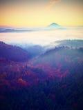 Nebelhafter Tagesanbruch in schöne Hügel Abstufung von bunten Wolken Lizenzfreies Stockfoto