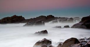Nebelhaftes Meer und Felsen Stockbilder