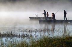 Nebelhaftes Sonnenaufgangfischen auf See lizenzfreie stockfotos