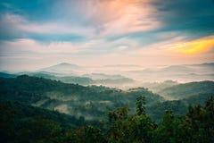 Nebelig in den Bergen mit drastischem Himmel bei Sonnenaufgang stockbild