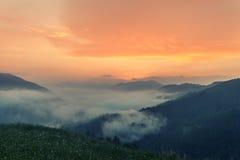 Nebelige Berglandschaft unter Morgenhimmel Lizenzfreie Stockfotos