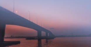 Nebelige Brücke während des Sonnenuntergangs Stockfotografie