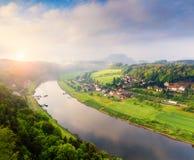 Nebelige Frühlingsansicht von Rathen-Dorf vom Standpunkt von Bastei herein stockfotos