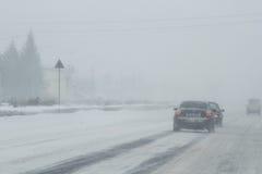 Nebelige, geschneite Straße mit niedrigem visbility Lizenzfreie Stockfotografie