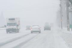 Nebelige, geschneite Straße mit niedrigem visbility Lizenzfreie Stockfotos