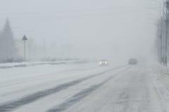 Nebelige, geschneite Straße mit niedrigem visbility Stockfoto