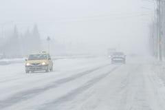 Nebelige, geschneite Straße mit niedrigem visbility Lizenzfreies Stockbild