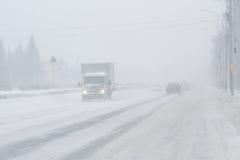 Nebelige, geschneite Straße mit niedrigem visbility Stockfotografie