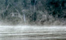 Nebelige Kabine im Wald Stockfotografie