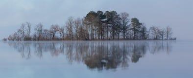 Nebelige reflektierende Insel auf ruhigem glasigem Wasser Lizenzfreies Stockfoto