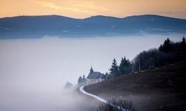 Nebelige Winterdämmerung mit Kapelle auf dem Abhang Stockbild