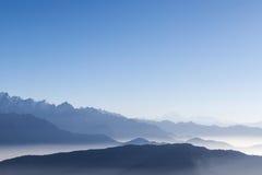 Nebeliger Gebirgszughintergrund mit blauem Himmel und Stockfotos