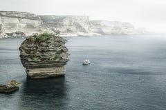 Nebeliger Meerblick mit einem Boot Stockfotos