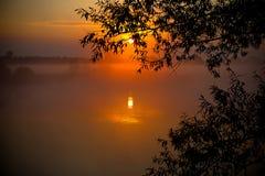 Nebeliger Sonnenaufgang über dem See Stockfoto