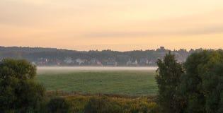 Nebeliger Sonnenaufgang über Dorf Stockbild