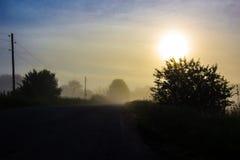 Nebeliger Sonnenaufgang auf der Straße Stockfoto
