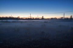 Nebeln Sie in der arktischen Tundra mit Stromleitungen ein Stockbilder