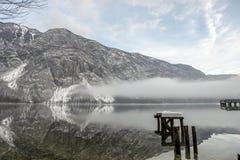 Nebelrollen herein auf Wasser unter Bergen Stockbild