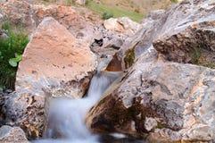 Nebenfluss, der zwischen die Steine läuft Stockbilder