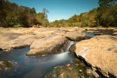 Nebenfluss und geschaukelt mit glattem Fluss und Fallwald stockfotografie
