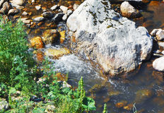 Nebenfluss unter Steinen Stockfotografie