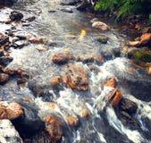 Nebenfluss unter Steinwasser im Sommer Lizenzfreie Stockbilder