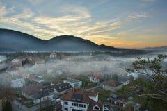 Neblina del otoño sobre una pequeña ciudad Imágenes de archivo libres de regalías
