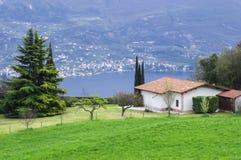 田园诗意大利农村风景绿色草坪,针叶树, nebolshoy有铺磁砖的屋顶的白色房子在背景中是湖加尔达 图库摄影