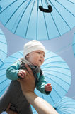 Neborn baby under a blue umbrellas. Royalty Free Stock Photo