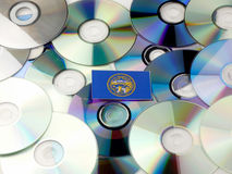 Nebraska flag on top of CD and DVD pile isolated on white. Nebraska flag on top of CD and DVD pile isolated Stock Images