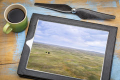 Nebraska Sandhills aerial view. Landscape of Nebraska Sandhills with two lonely trees, reviewing aerial image on a digital tablet with a cup of coffee Stock Photo