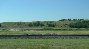 Nebraska Sandhills in rural central Nebraska, with railroad tracks. Rural scenery of the Sandhills of Nebraska with railroad tracks, blue skies, sparse trees and Royalty Free Stock Photos