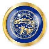 Nebraska Flag Button. Nebraska state flag button with a gold metal circular border over a white background Stock Photography