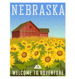 Nebraska travel poster. Sunflowers in front of old red barn. Royalty Free Stock Image