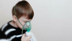Nebulizer και inhaler χρήσης για την επεξεργασία Αγόρι που εισπνέει μέσω inhaler της μάσκας Πλάγια όψη απόθεμα βίντεο