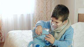 Nebulizer dla inhalaci, chory dziecko oddycha przez nebulizer, dziecko robi inhalaci, chłopiec z maską tlenową na jego zbiory wideo
