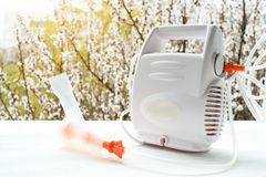 Nebulizer with a mask on the background of a blossoming tree. Spring exacerbation.  stock photos