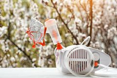 Nebulizer with a mask on the background of a blossoming tree. Spring exacerbation.  royalty free stock photo