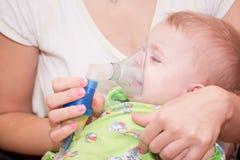 Nebulizer. Mom makes inhalation child nebulizer Stock Image
