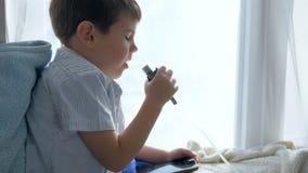 Nebulizers η θεραπεία, ασθενές αγόρι με το smartphone διαθέσιμο αναπνέει μέσω ενός εισπνευστικού για τη θεραπεία φιλμ μικρού μήκους