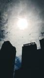 Nebuloso com o obscuro da luz do sol está sobre a construção Foto de Stock