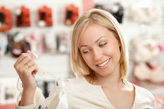 That is necessary!. The woman looks at a brassiere in shop and smiles Stock Photography