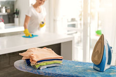 Necessary duties for modern housewife. Smiling woman is cleaning white countertop with blue rag. Focus on iron and coloured clothes at pressboard. Copy space Royalty Free Stock Photos
