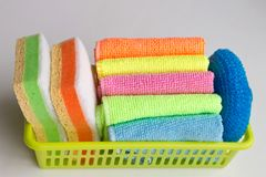 In the basket are multi-colored sponges and cleaning rags stock images